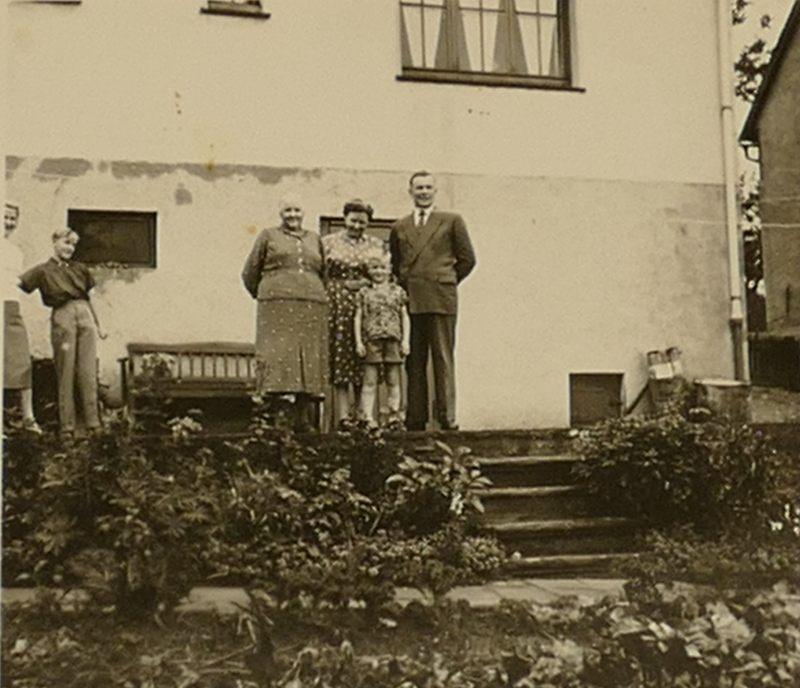 Oma Weber mit Lappen hinter Lappen Haus
