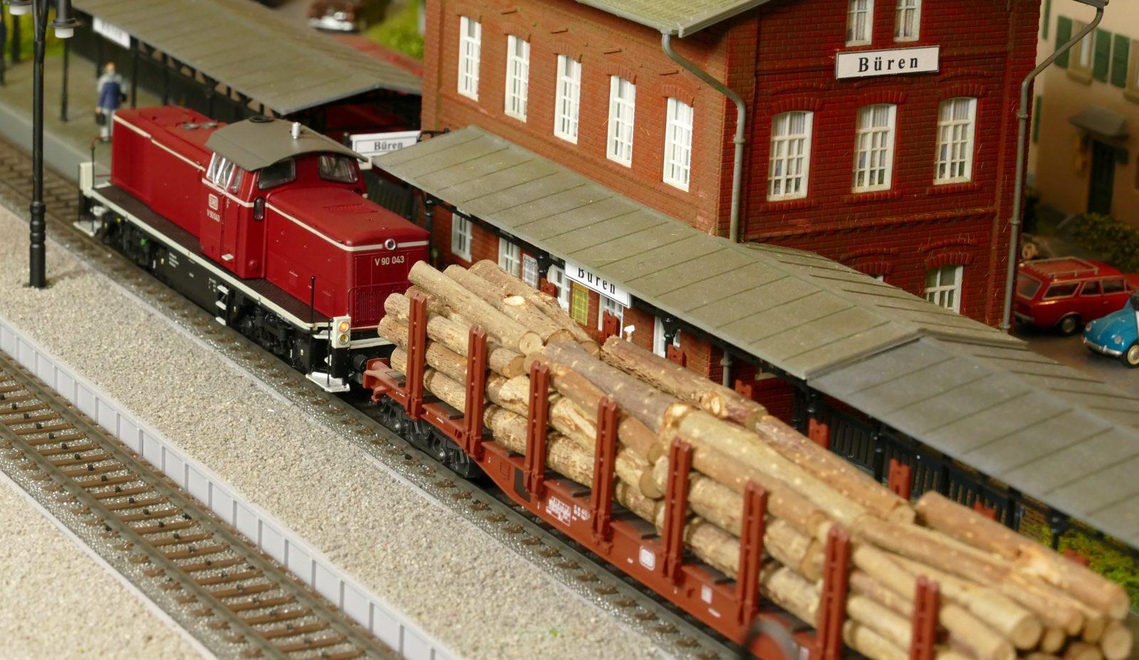 Eine V90 zieht einen langen Holzzug durch den Bürener Bahnhof
